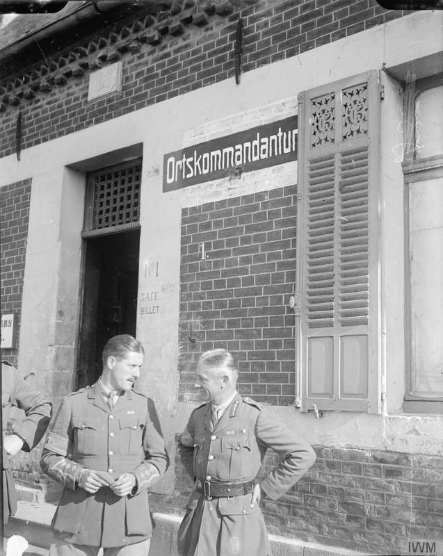 Brigadier General W M Withycombe (right), 107th Brigade, 36th (Ulster) Division, outside the former German town mayor's house in Metz-en-Couture, 17 October 1917. IWM Q 7244.